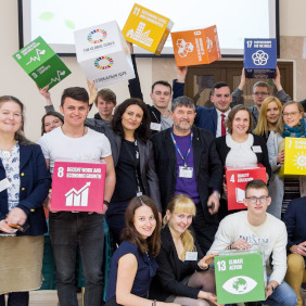 Students and teachers holding SDG boxes